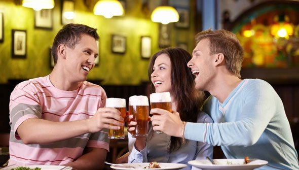 Three friends enjoying a beer at the bar
