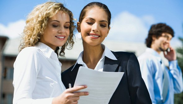 Two women reviewing a residential rental application happily